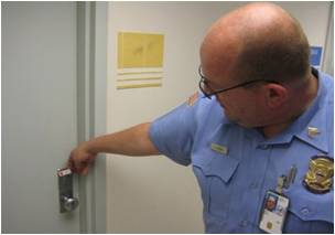 Police officer placing a red seal on a door
