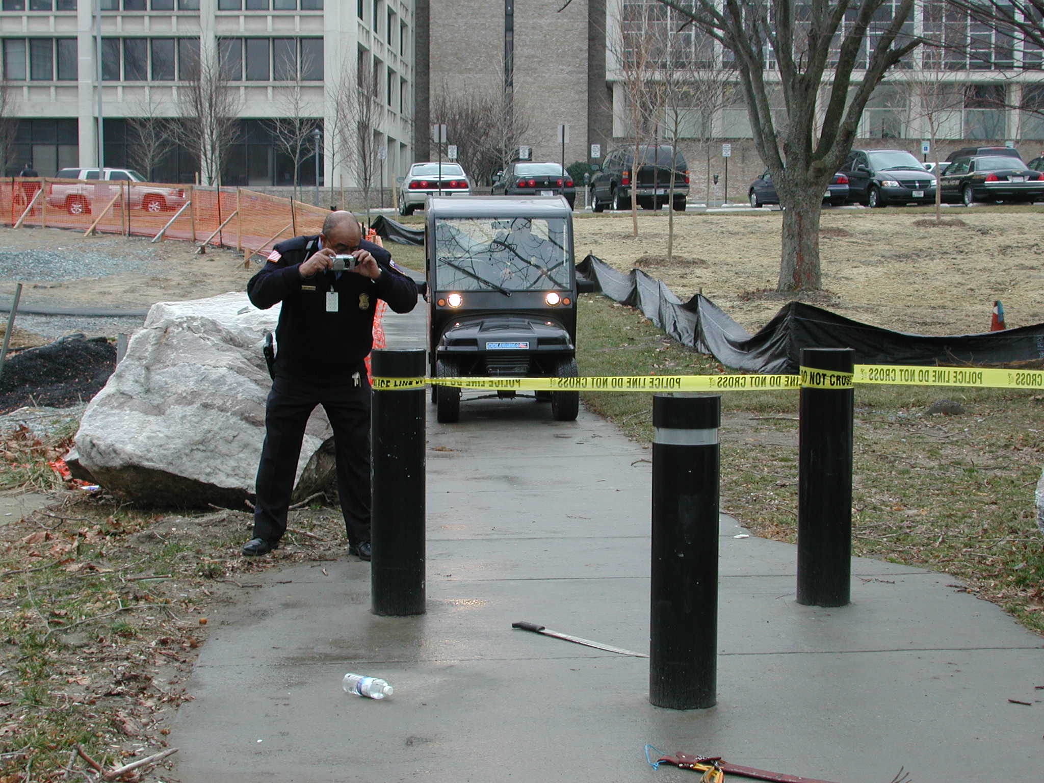 Outdoor crime scene officer taking a phot and police cart arriving 2.JPG