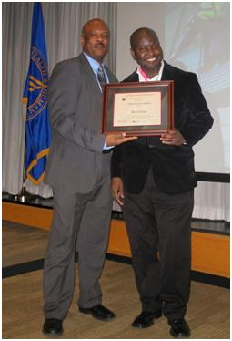 Two men standing up, holding an award