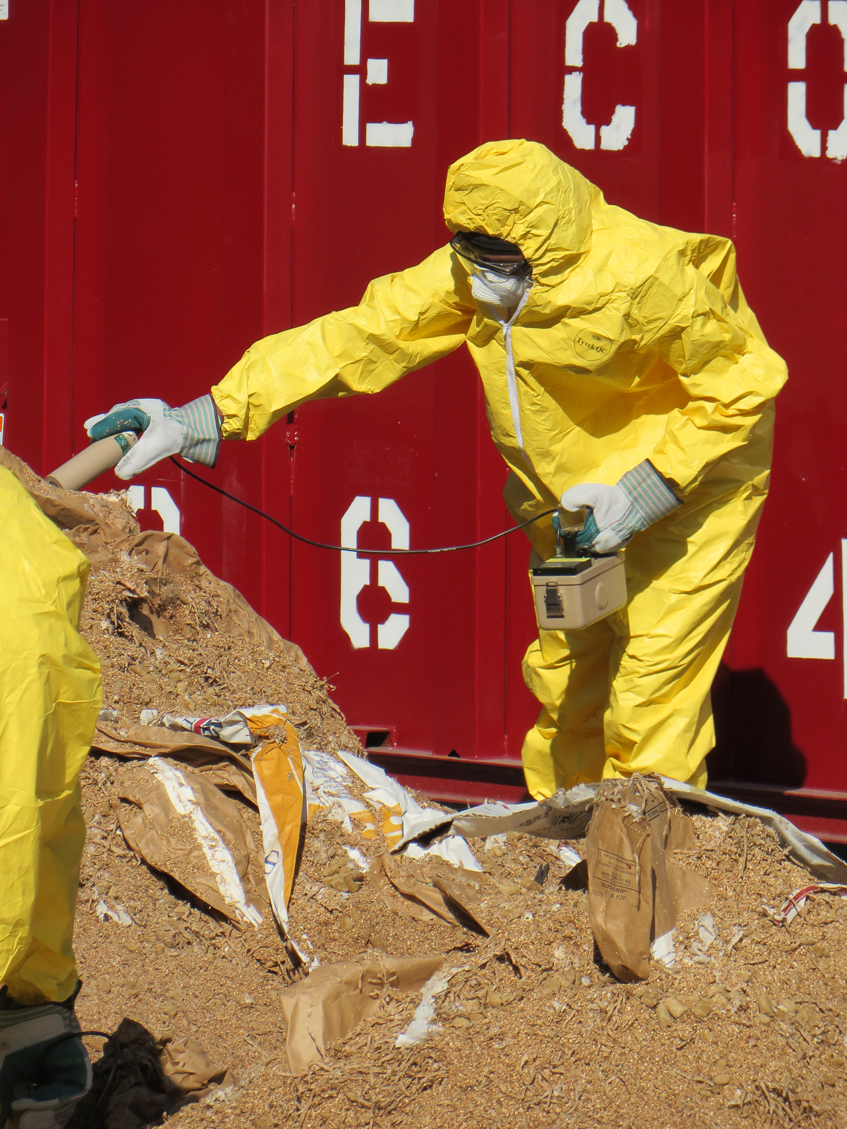 Person in Hazmat uniform using a machine